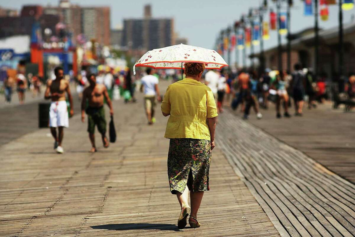 NEW YORK, NY - JULY 12: A woman walks down the boardwalk in Coney Island on July 12, 2012 in the Brooklyn borough of New York City. Coney Island has until recently been viewed as a seedy and dilapidating seaside park, however, it is going through a gradual transition which many compare to the renovation of Times Square. In order to accommodate more shops and residential buildings, the Michael Bloomberg administration rezoned Coney Island in 2009. The city also bought seven acres of prime Coney Island real estate promising approximately $150 million in infrastructure upgrades in the area. A recent study found that Coney Island's Luna Park had 640,000 visitors in 2011, the most since Steeplechase Park closed in 1964.