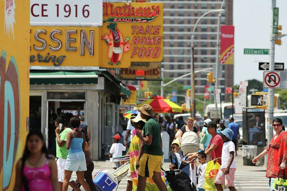 NEW YORK, NY - JULY 12:  People walk along a street at Coney Island on July 12, 2012 in the Brooklyn borough of New York City. Coney Island has until recently been viewed as a seedy and dilapidating seaside park, however, it is going through a gradual transition which many compare to the renovation of Times Square. In order to accommodate more shops and residential buildings, the Michael Bloomberg administration rezoned Coney Island in 2009. The city also bought seven acres of prime Coney Island real estate promising approximately $150 million in infrastructure upgrades in the area. A recent study found that Coney Island's Luna Park had 640,000 visitors in 2011, the most since Steeplechase Park closed in 1964. Photo: Spencer Platt, Getty Images / 2012 Getty Images
