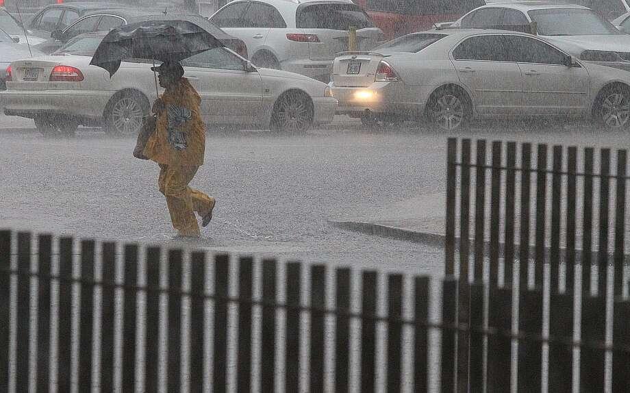 A pedestrian crosses Preston during a heavy downpour. (Nick de la Torre/Chronicle)