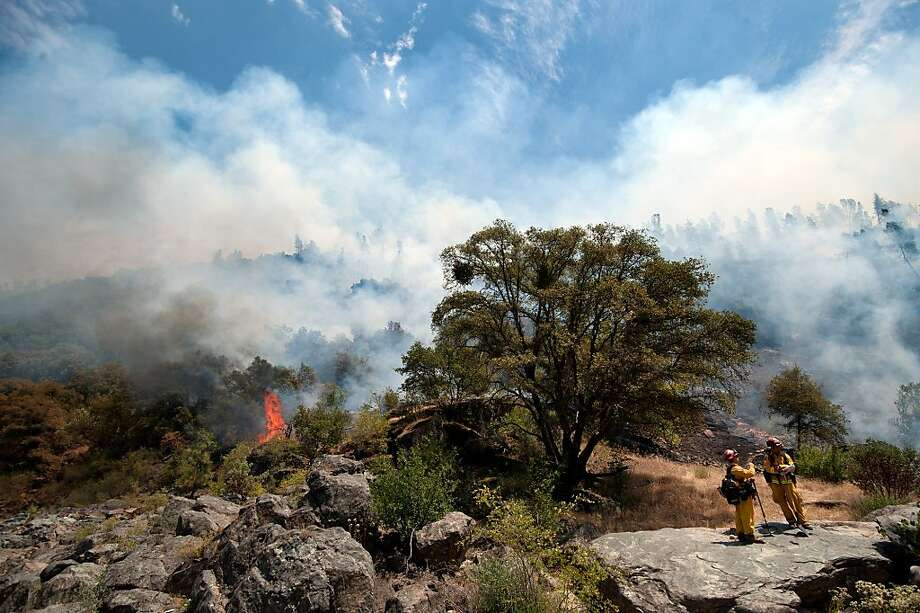 Two Cal Fire captains talk while fire burns on a steep hillside near Yankee Jim's Road in Placer County, Calif., next to the north fork of the American River, Thursday, July 12, 2012. Firefighter's are hoping to keep the fire contained to the east side of the river. About 300 people in Placer County remained under evacuation orders as a fire burning in a steep, heavily wooded area grew in size and intensity, fueled by hot weather and wind. Photo: Randy Pench, Associated Press