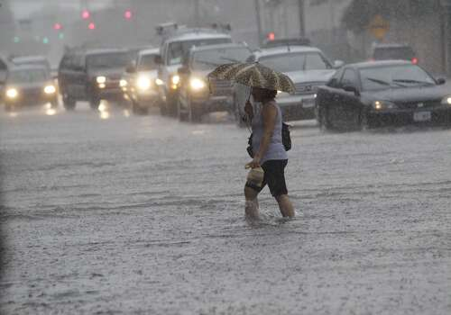 A woman crosses along San Jacinto at Elgin Friday morning. (Melissa Phillip/Chronicle) Photo: Melissa Phillip, Houston Chronicle