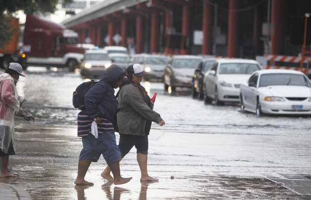 Two people cross the street at Texas and Chartres along U.S. 59 Friday. (Mayra Beltran/Chronicle) Photo: Mayra Beltran, Houston Chronicle