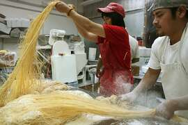 Owner Xin Feng Liu (left) of the North American Noodle Company preparing noodles for packaging in San Francisco, Calif., on Tuesday,  July 10, 2012.