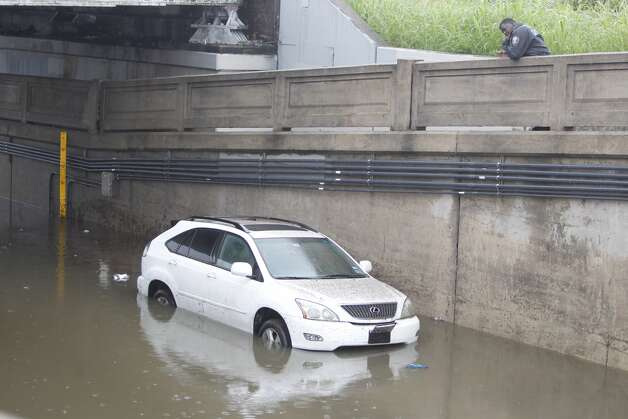 A Lexus SUV is trapped in flooded waters in Houston after a series of storms continued to dump water on the region.