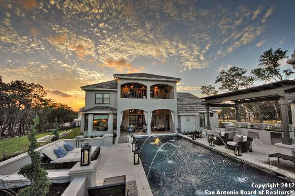 A look at the rear exterior of the property, spotlighting the architecture of the home while looking down the length of the swimming pool and patio.