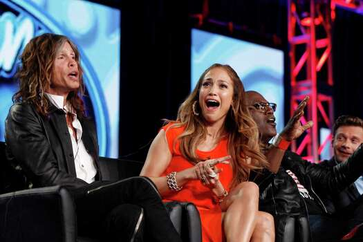 "FILE - In this Jan. 8, 2012 photo, ""American Idol"" judge Jennifer Lopez, center, reacts as fellow judge Steven Tyler, left, of Aerosmith makes a joke about wearing Lopez's pants as Randy Jackson and Ryan Seacrest are seen at right during the ""American Idol"" panel at the Fox Broadcasting Company Television Critics Association Winter Press Tour in Pasadena, Calif. ""American Idol"" is on the brink of a crisis, Thursday, July 12, 2012, as judge Steven Tyler is leaving, and fellow judge Jennifer Lopez is dithering about staying put. (AP Photo/Danny Moloshok, File) Photo: Danny Moloshok"