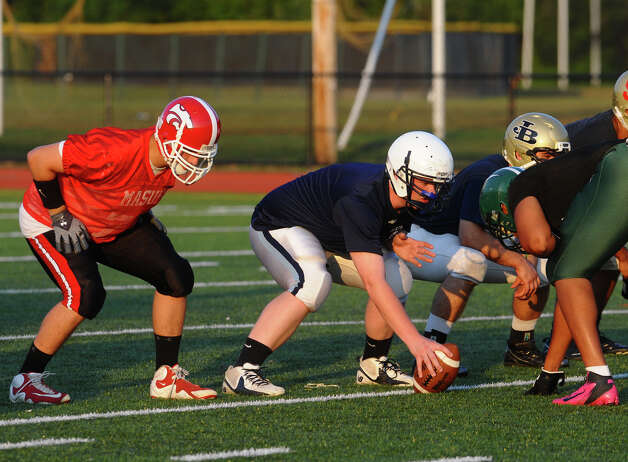 Wilton's Hunter Geraghty snaps the ball at Fairfield County All-Star football practice at St. Joseph High School in Trumbull, Conn. on Thursday July 12, 2012. Photo: Christian Abraham / Connecticut Post