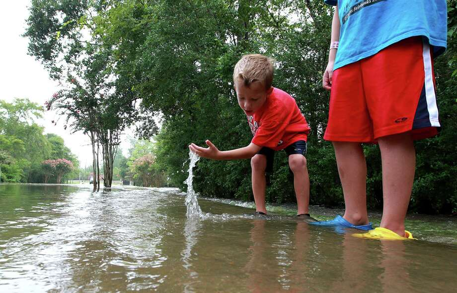 Adam Lancaster, 7, left, plays with his cousin Benjamin Lancaster, 10, right on Longwood Trace Drive in the Longwood neighborhood as floodwaters from the Little Cypress Creek flowed over its banks Friday, July 13, 2012, in Cypress. 