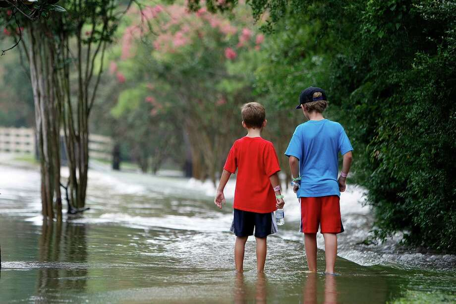 """Adam Lancaster, 7, left, and his cousin Benjamin Lancaster, 10, right try to spot fish on a flooded sidewalk on Longwood Trace Drive in the Longwood neighborhood as floodwaters from the Little Cypress Creek flowed over its banks Friday, July 13, 2012, in Cypress.  """"It's pretty cool,"""" Adam said. """"I saw fish."""" Photo: Johnny Hanson, Houston Chronicle / © 2012  Houston Chronicle"""