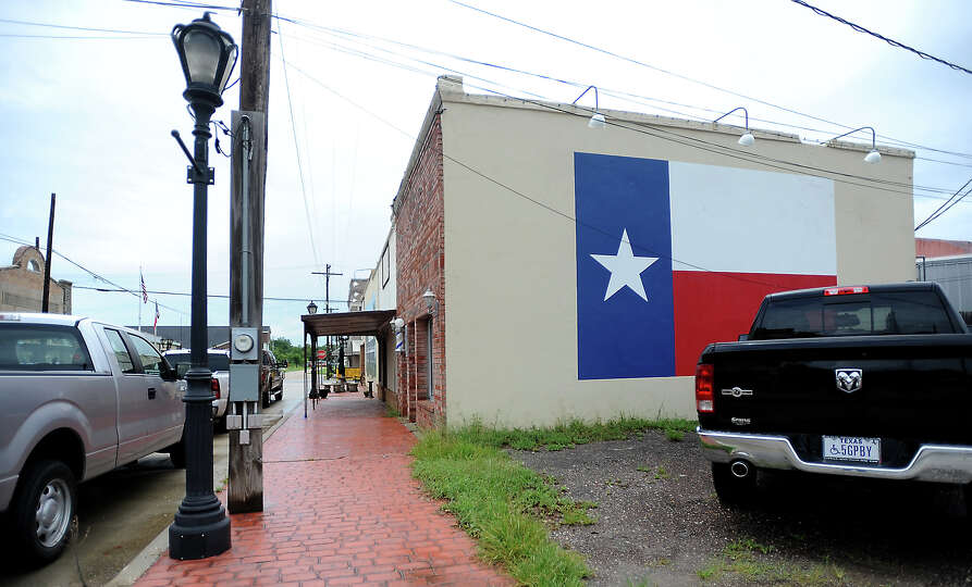 David Payne's barber shop has a large Texas flag mural painted on the side of his shop in Sour Lake,