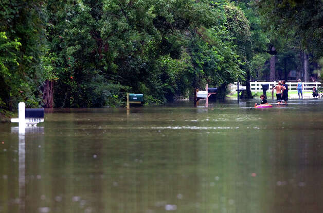 Nick Giacona, 11, sits in a raft on the flooded street of Pine Belt Drive Friday, July 13, 2012, in Cypress. Photo: Cody Duty, Houston Chronicle / © 2011 Houston Chronicle