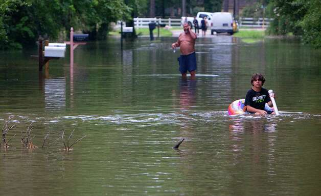Nick Giacona, 11, right, and Dennis Fulkert, left, are seen in the flooded street of Pine Belt Drive Friday, July 13, 2012, in Cypress. Photo: Cody Duty, Houston Chronicle / © 2011 Houston Chronicle