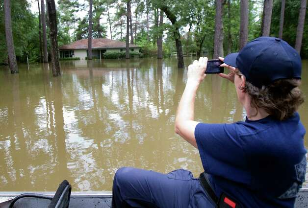 Harris County Sheriff's Department Marine Division Captain D. O'Leary takes a photo of a submersed home on the flooded street of Pine Belt Drive Friday, July 13, 2012, in Cypress. Photo: Cody Duty, Houston Chronicle / © 2011 Houston Chronicle