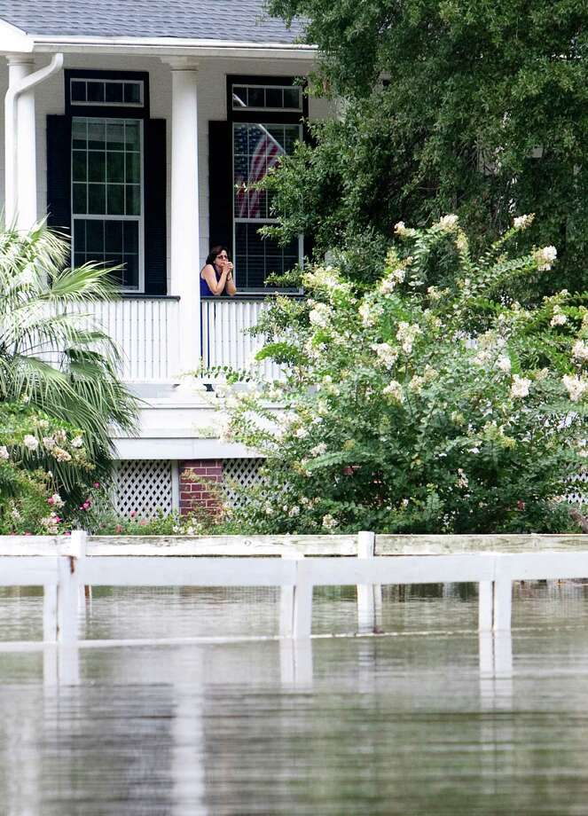 A woman stands in her home on the flooded street of Creekway Drive Friday, July 13, 2012, in Cypress. Photo: Cody Duty, Houston Chronicle / © 2011 Houston Chronicle