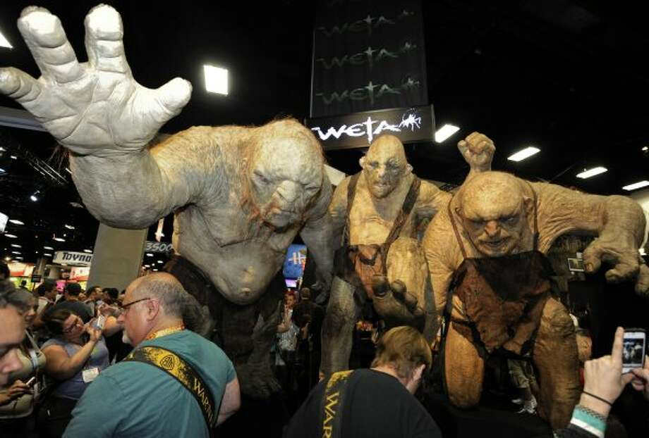 Fans walk past huge Stone Troll figures from the Lord of the Rings at the Comic-Con preview night held at the San Diego Convention Center on Wednesday July 11, 2012, in San Diego.  (Photo by Denis Poroy/Invision/AP) (DENIS POROY/INVISION/AP)