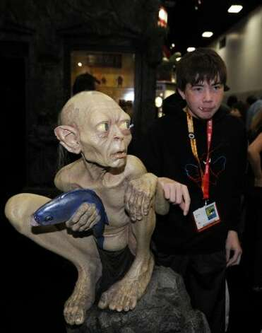 Christian Ash poses with a Gollum figure from the Lord of the Rings at the Comic-Con preview night held at the San Diego Convention Center on Wednesday July 11, 2012, in San Diego.  (Photo by Denis Poroy/Invision/AP) (DENIS POROY/INVISION/AP)