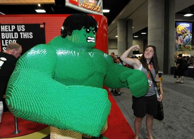 Abbey Stubblefield poses next to a LEGO Hulk figure in the exhibit hall on preview night at Comic-Con on at the San Diego Convention center Wednesday July 11, 2012, in San Diego.  (Photo by Denis Poroy/Invision/AP) (DENIS POROY/INVISION/AP)