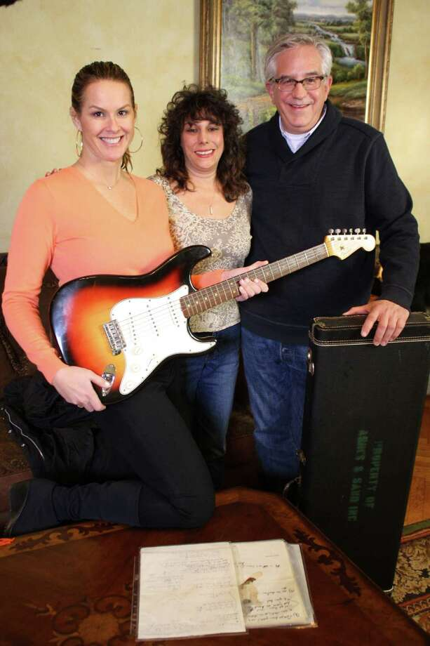 Elyse Luray (from left), guitar owner Dawn Peterson and  Wes Cowan with the electric guitar they says was Bob Dylan's.