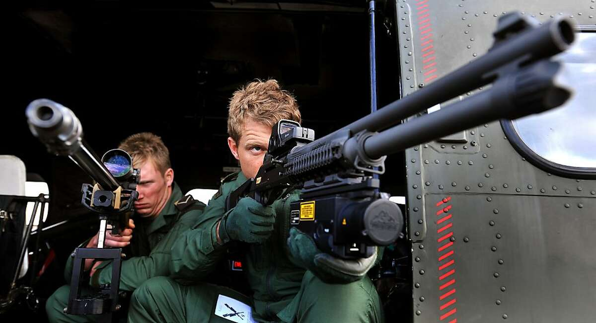 """Snipers with the Royal Air Force Regiment, look through the scopes of their sniper rifles as the military prepares for duty to provide security aboard helicopters high above the London Olympic games, at RAF Northolt, in London, Friday July 13, 2012. Aircraft that fail to comply with procedures within a restricted airspace zone around the Olympic venues could be subject to """"lethal force"""" from the military, it is revealed Friday. RAF Typhoon fast jets and RAF Puma helicopters with snipers armed with hi-tech rifles will be among the military aircraft patrolling the restricted zone which comes into force during the London 2012 Olympic Games. (AP Photo/John Stillwell, PA) UNITED KINGDOM OUT - NO SALES - NO ARCHIVE"""