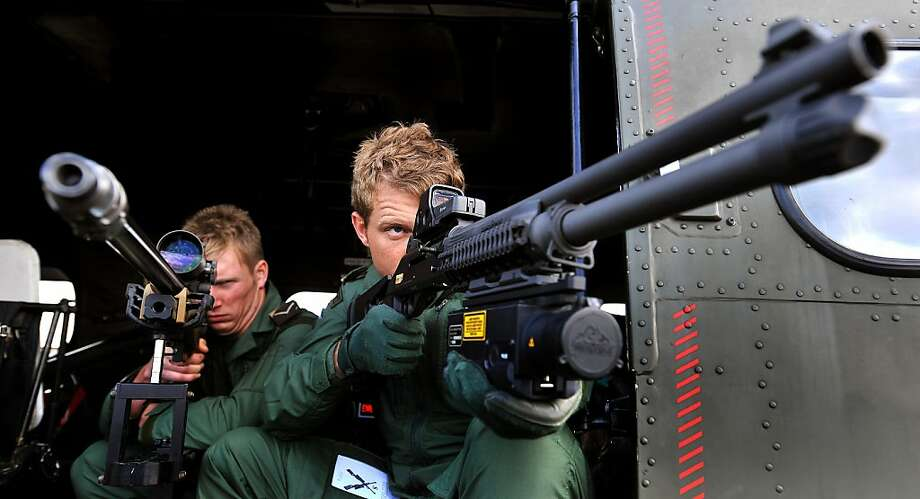 """Snipers with the Royal Air Force Regiment, look through the scopes of their sniper rifles as the military prepares for duty to provide security aboard helicopters high above the London Olympic games, at RAF Northolt, in London, Friday July 13, 2012. Aircraft that fail to comply with procedures within a restricted airspace zone around the Olympic venues could be subject to """"lethal force"""" from the military, it is revealed Friday. RAF Typhoon fast jets and RAF Puma helicopters with snipers armed with hi-tech rifles will be among the military aircraft patrolling the restricted zone which comes into force during the London 2012 Olympic Games. (AP Photo/John Stillwell, PA) UNITED KINGDOM OUT - NO SALES - NO ARCHIVE Photo: John Stillwell, Associated Press"""