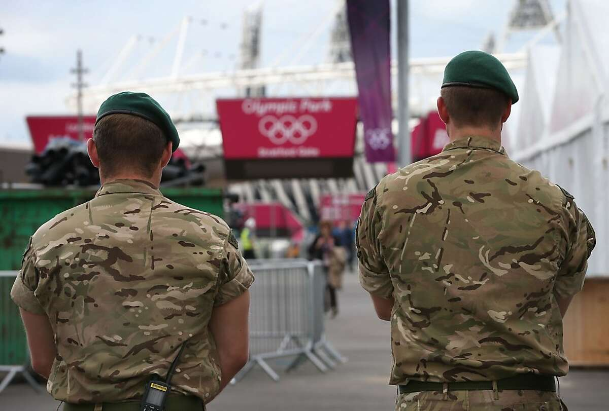 LONDON, ENGLAND - JULY 13: Soldiers guard an exit from the Olympic Park on July 13, 2012 in London, England. An extra 3500 soldiers are to be deployed to guard the London 2012 Olympic Games after private security contactor G4S failed to recruit enough personnel. (Photo by Peter Macdiarmid/Getty Images)