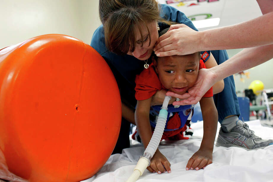 Physical therapist Selina Morgan lifts Braylon Nelson with the help of occupational therapist Revi Hawley at Santa Rosa Children's Hospital in July. Photo: Lisa Krantz, San Antonio Express-News / San Antonio Express-News