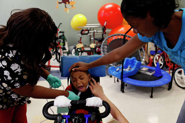 Braylon, riding a modified bicycle during therapy, cries in frustration as Battle suctions his tracheotomy tube to clear mucus while his mother Candice Matthews (right) comforts him. Photo: Lisa Krantz, San Antonio Express-News / San Antonio Express-News