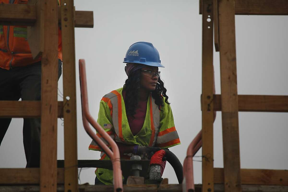 Oakland resident Tiffany West, Flatiron carpenter apprentice, cleans a bent cap as she works on the Oakland Airport Connector project on Hegenberger Road on Friday, July 13, 2012 in Oakland, Calif.