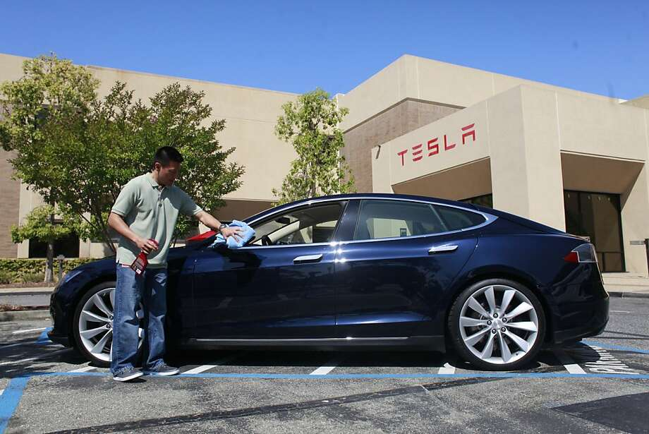Jason Noma, with Tesla Sales, shines the new Tesla Model S sedan at the Tesla Headquarters. Photo: Mike Kepka, The Chronicle