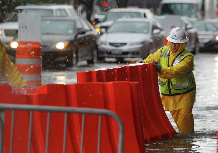 Jose Orsoto pushes a barricade that became floating devices when Chartres Street flooded at Texas Avenue on Friday, July 13, 2012, in Downtown Houston. Photo: Mayra Beltran, Houston Chronicle / © 2012 Houston Chronicle