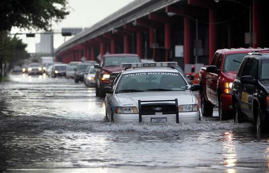 Traffic travels slowly northbound on Chartres Street intersecting with Texas Avenue after heavy rain flooded parts of Downtown Houston on Friday, July 13, 2012. Photo: Mayra Beltran, Houston Chronicle / © 2012 Houston Chronicle