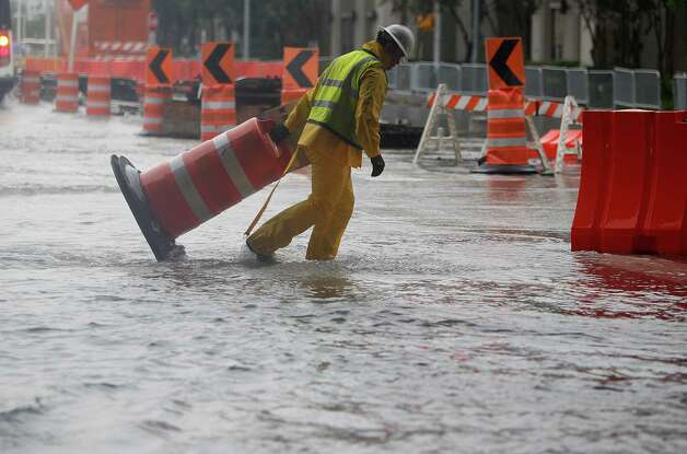 Donovan Trevino clears the street from barricades that became floating devices when Chartres Street flooded at Texas Avenue on Friday, July 13, 2012, in Downtown Houston. Photo: Mayra Beltran, Houston Chronicle / © 2012 Houston Chronicle