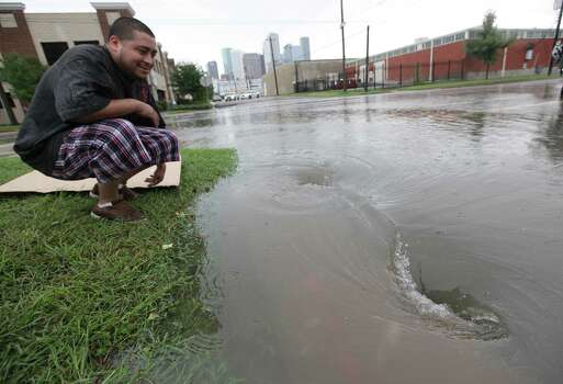 A man views the water draining along Dowling Street east of Downtown Houston on Friday, July 13, 2012, in Houston. ( Mayra Beltran / Houston Chronicle )
