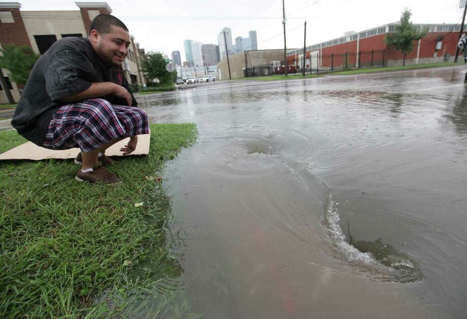 A man views the water draining along Dowling Street east of Downtown Houston on Friday, July 13, 2012, in Houston. ( Mayra Beltran / Houston Chronicle ) (Man didn't want to be identified) Photo: Mayra Beltran, Houston Chronicle / © 2012 Houston Chronicle