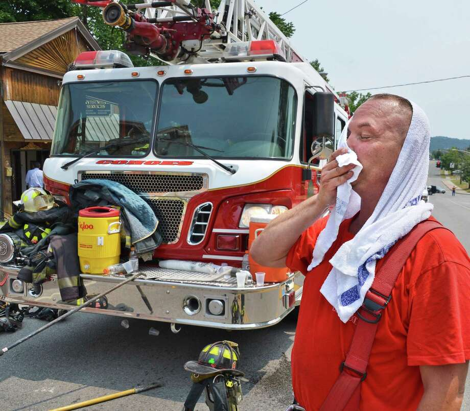 Cohoes firefighter Dean Plowman cools off with a wet towel after his department made short work of a fire at the Hair by Alan salon on North Mohawk St. in Cohoes Friday July 13, 2012.   (John Carl D'Annibale / Times Union) Photo: John Carl D'Annibale