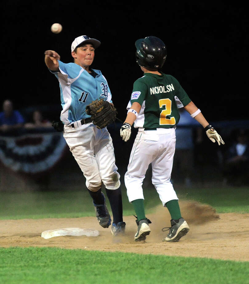 Wilton's Collin Kahal throws to first after getting National Lione's Conor Nicholson out at second base during Friday's District 1 Little League Championship game at Springdale Little League Field in Stamford on July 13, 2012. Photo: Lindsay Niegelberg / Stamford Advocate