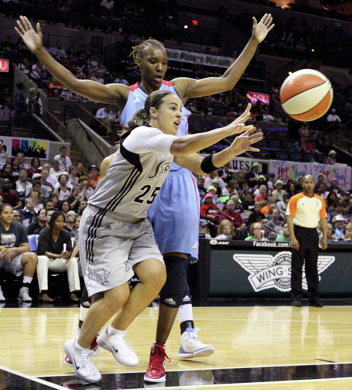 Silver Stars' Becky Hammon passes around Dream's Sancho Lyttle during first half action Friday, July 13, 2012 at the AT&T Center.