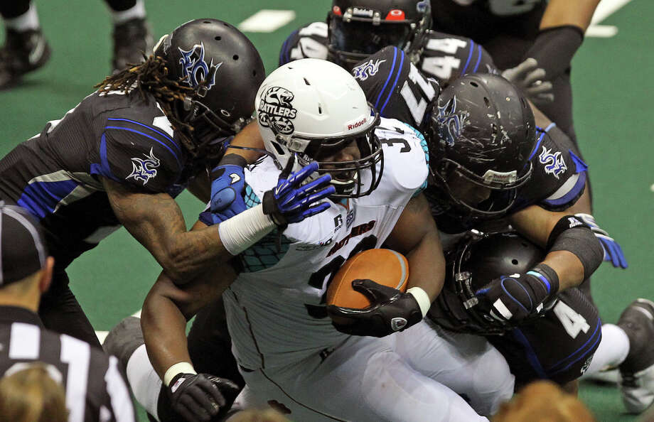 Rattlers fullback Odie Armstrong is swamped by Talon defenders as the Talons host the Arizona Rattlers at the Alamodome  on July 13, 2012. Photo: Tom Reel, Express-News / ©2012 San Antono Express-News