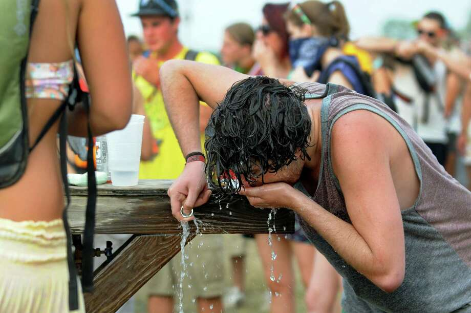 Graham Keenan, 21, of Westchester cools down at a water spout at Camp Bisco on Friday, July 13, 2012, at Indian Lookout Country Club in Mariaville, N.Y. (Cindy Schultz / Times Union) Photo: Cindy Schultz / 00018447A