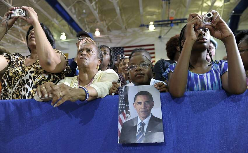 People watch as President Barack Obama speaks at a campaign event at Phoebus High School in Hampton, Va., Friday, July 13, 2012. Obama is spending the day in Virginia campaigning. (AP Photo/Susan Walsh)