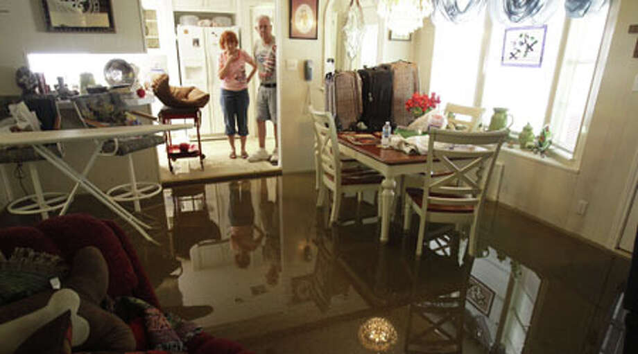 Janet and Jerry Turner wait to have water removed from their flooded home on Pine Belt on Saturday, July 14, 2012, in Cypress.  Photo: .