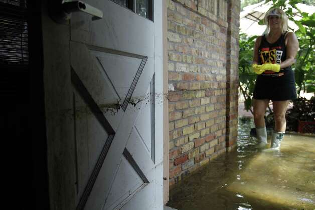 Jeannette Harris shows the three-foot mark from flooding on her garage door Saturday on Hickory Hill in the Windwood subdivision in Cypress. She said the home has flooded four times in 18 years. Photo: .