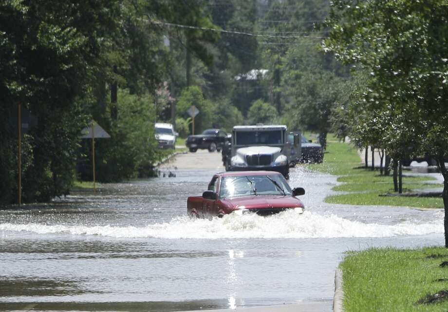 A truck drives through Cypress Creek flooding along Grant Road on Saturday in Cypress. Photo: .