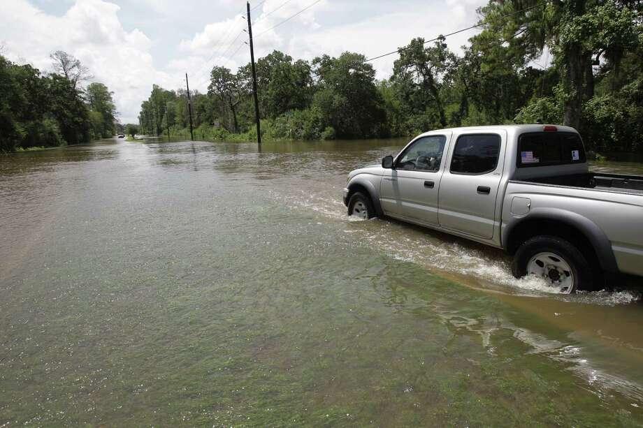 A truck drives through Cypress Creek flood waters along Grant Road near Oak Hallow on Saturday in Cypress. Photo: .