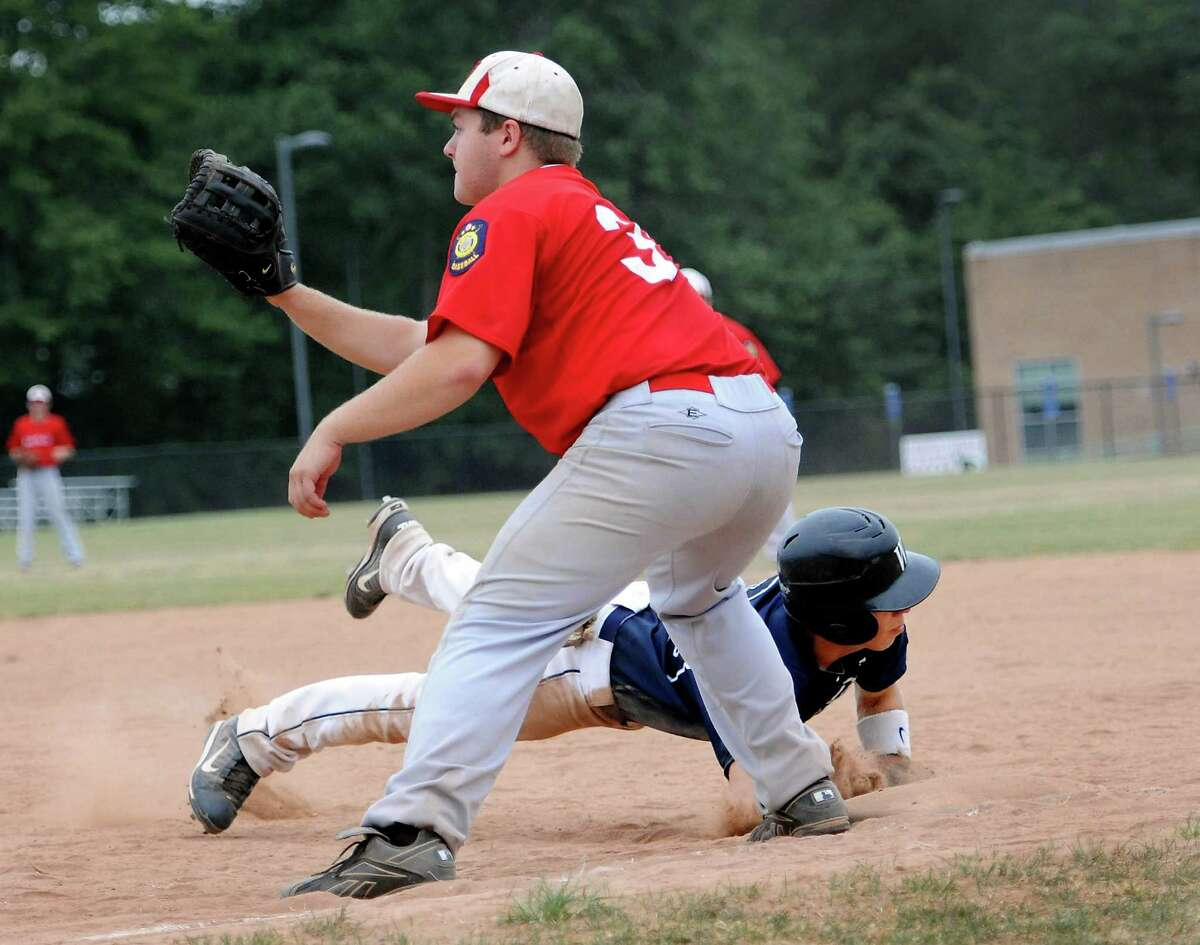 Matt Campbell of the Westport Senior Legion baseball team beats out a pick off throw to Fairfield first baseman Tim Moran during a game held at Fairfield Warde High School, Fairfield, CT on Friday July 13th, 2012