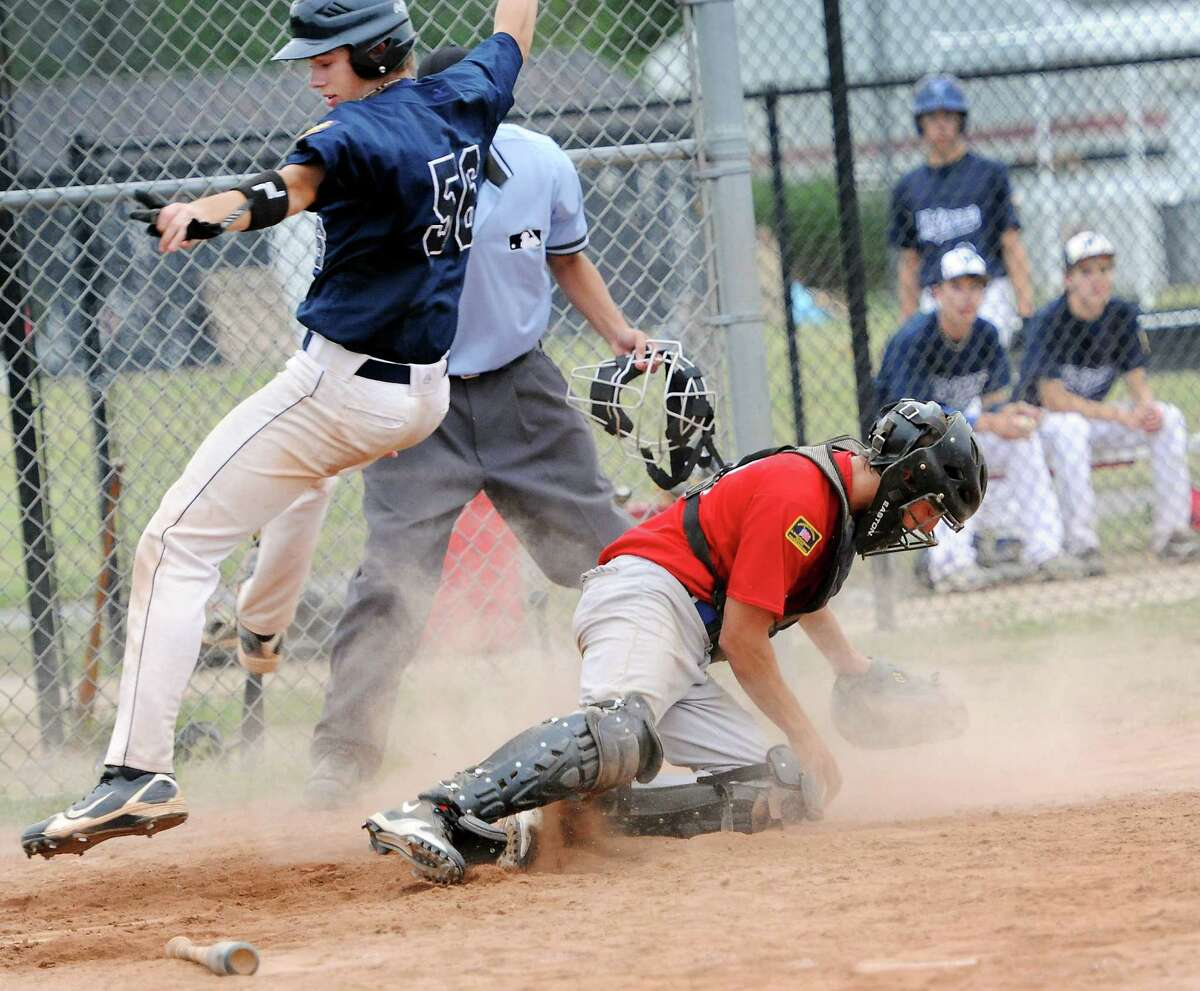 Juliane Clarke of the Westport Senior Legion baseball team gets by Fairfield catcher Sam Kivell and scores on a close play at the plate during a game against the Fairfield team held at Fairfield Warde High School, Fairfield, CT on Friday July 13th, 2012.