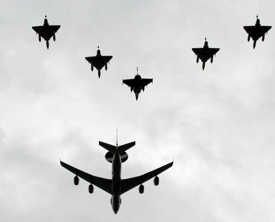 French Air Force jet fighters Rafale, center, and Mirages 2000 perform with an E3F Awacs, during the traditional Bastille Day parade over the Champs Elysee in Paris, Saturday July 14, 2012. Photo: Remy De La Mauviniere, Associated Press / AP