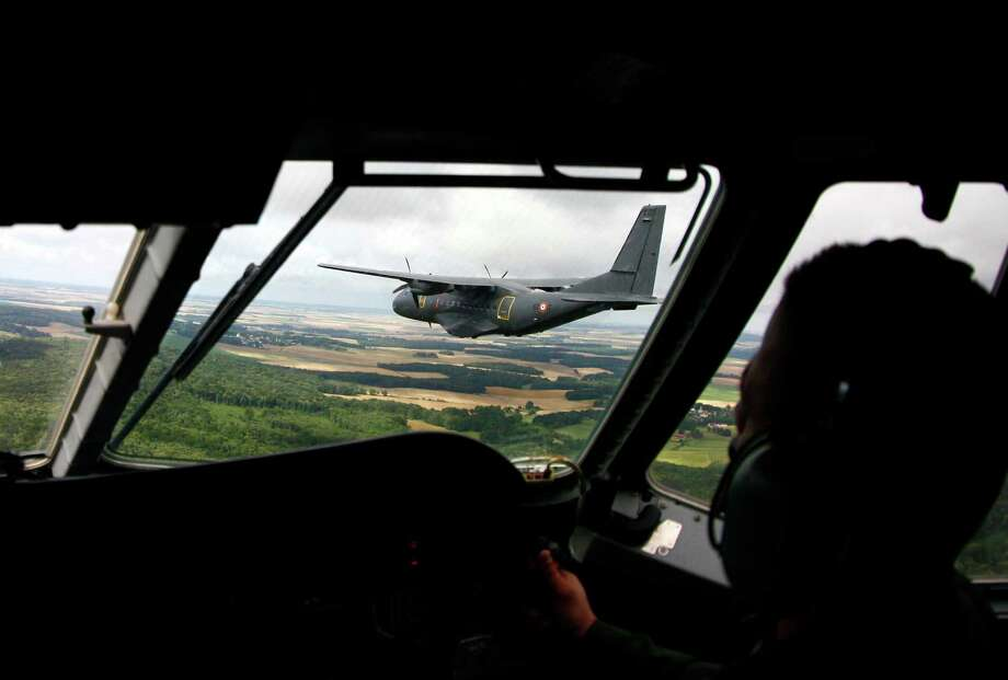 A military troop carrier flies north of Paris before participating in a flyover for the Bastille Day military parade, Saturday, July 14, 2012. Photo: Michel Spingler, Associated Press / AP