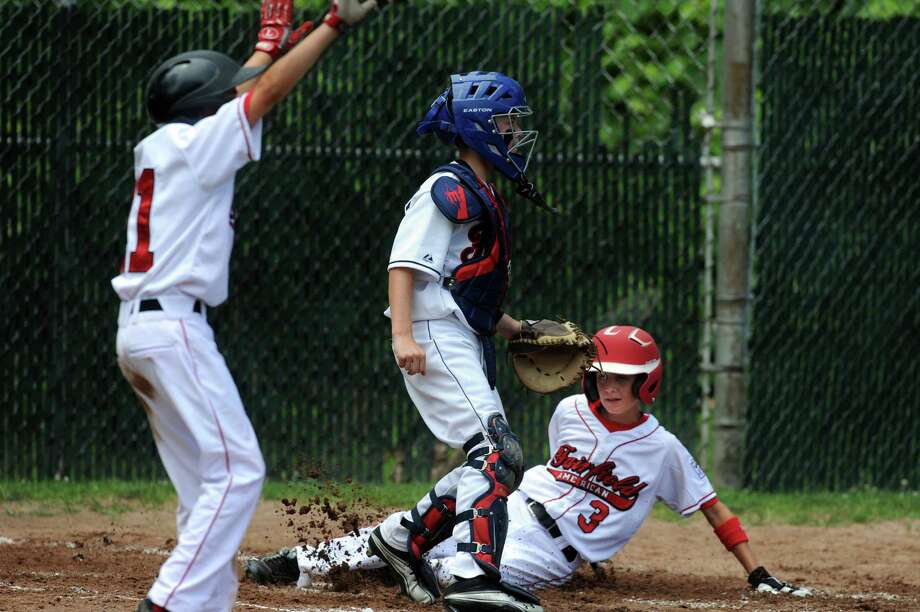 Fairfield American's Chris Meyers slides home as teammate Matty Clarkin, far left, cheers and Fairfield National's Tyler Llewellyn waits for the ball during the District 2 Little League Championship Saturday, July 14, 2012 in Bridgeport, Conn. Photo: Autumn Driscoll / Connecticut Post