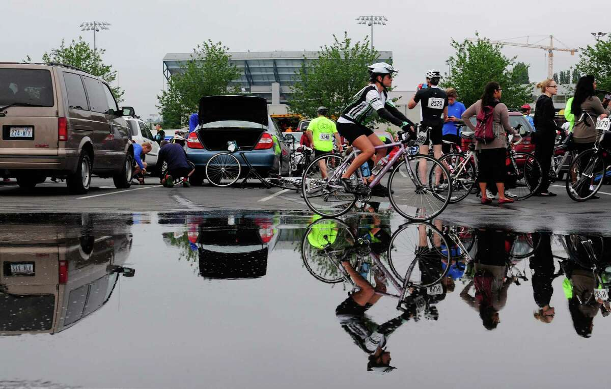 A bicyclist rides through a large puddle in the parking lot that served as at the start at the University of Washington.